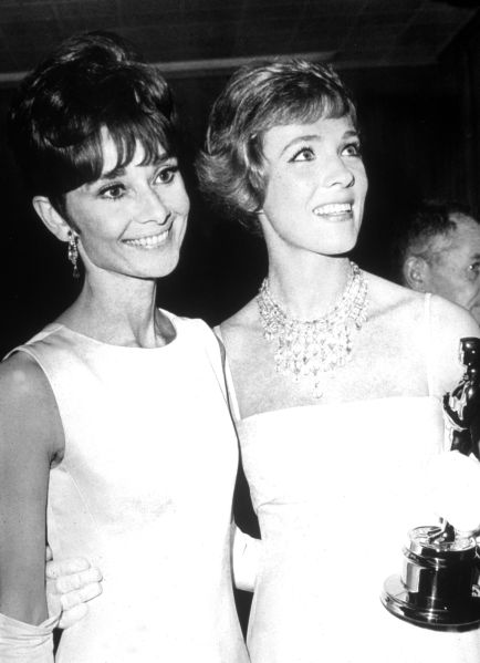 British actor Julie Andrews (right) holds her Oscar while standing with Belgian born actor Audrey Hepburn (1929 - 1983) at the Academy Awards ceremonies in Santa Monica, California, April 5, 1965. Andrews won Best Actress for her performance in the film, 'Mary Poppins,' directed by Robert Stephenson.