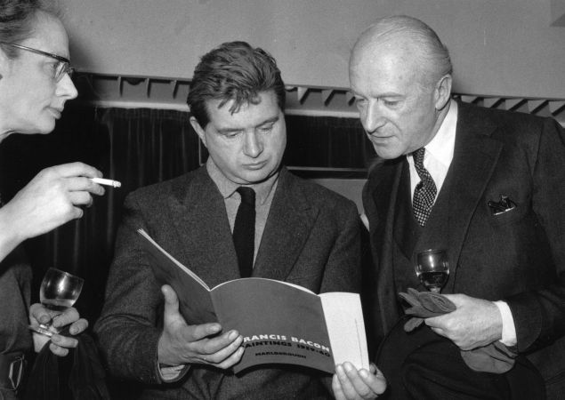 Irish painter Francis Bacon (1909 - 1992) (centre), reading his exhibition catalogue, and English photographer Cecil Beaton at the Marlborough Gallery, London. (Photo by Evening Standard/Getty Images)