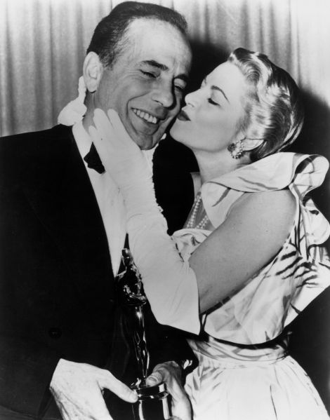 1952: American actor Humphrey Bogart (1899-1957) receives a kiss from actor Claire Trevor (1909 - 2000) while standing backstage with the Best Actor Oscar he won for his role in director John Huston's film, 'The African Queen,' RKO Pantages Theatre, Los Angeles, California.