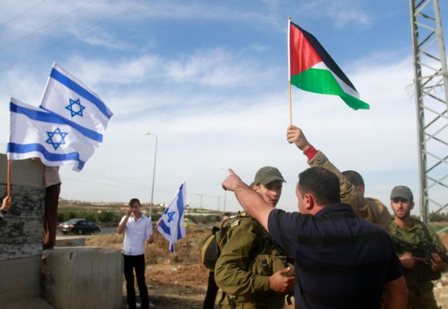 A Jewish settler (L unseen) places the Israeli flag on a road sign while Israeli troops encircle Palestinian villagers protesting after the Israeli army cut off branches of olive trees.