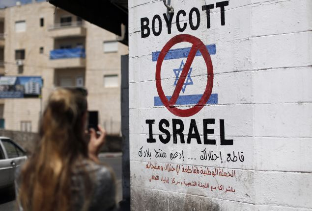 A tourist photographs a sign painted on a wall in the West Bank biblical town of Bethlehem on June 5, 2015, calling to boycott Israeli products coming from Jewish settlements. The international BDS (boycott, divestment and sanctions) campaign, that pushes for a ban on Israeli products, aims to exert political and economic pressure over Israel's occupation of the Palestinian territories in a bid to repeat the success of the campaign which ended apartheid in South Africa. AFP PHOTO / THOMAS COEX (Photo credit should read THOMAS COEX/AFP/Getty Images)