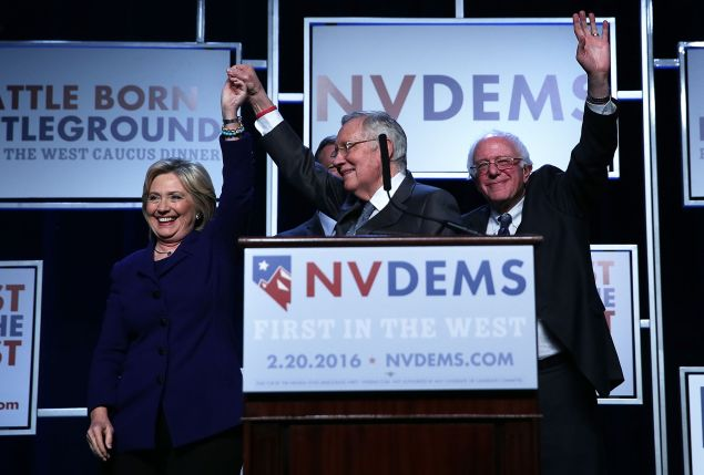 Democratic Presidential candidates Hillary Clinton and Sen. Bernie Sanders on stage with Senate Minority Leader Harry Reid prior to the Battle Born/Battleground First in the West Caucus Dinner at the MGM Grand January 6, 2016 in Las Vegas, Nevada. The three candidates continue to campaign prior to the Nevada Democratic caucus, which will take place on February 20, 2016.
