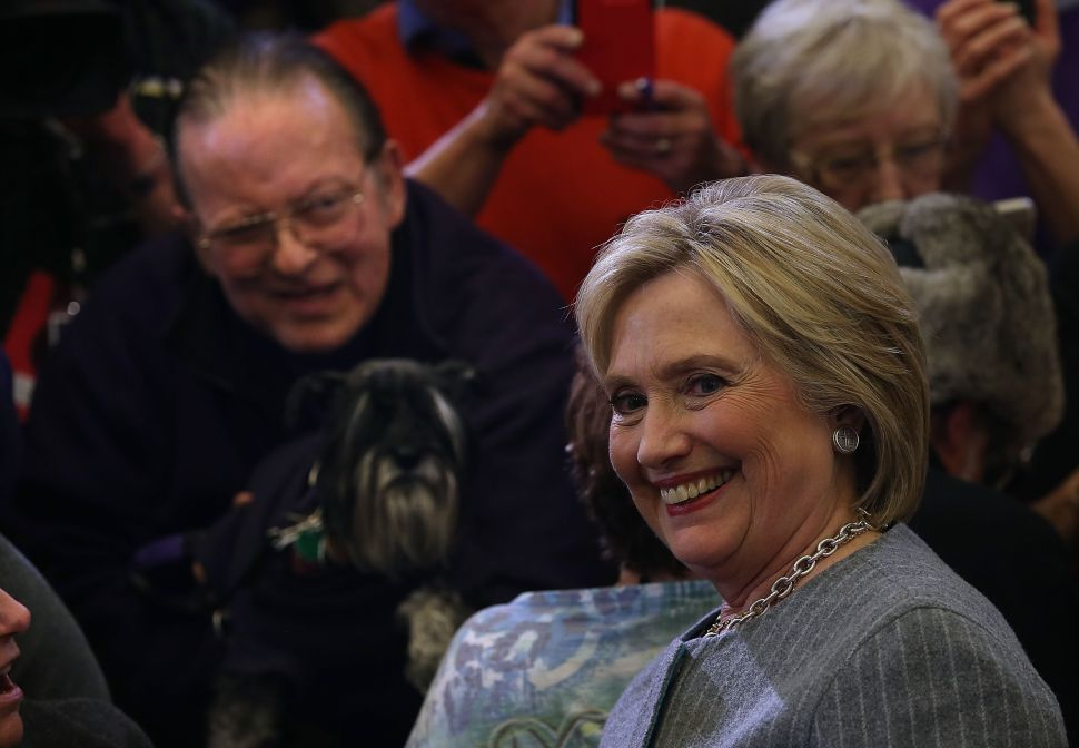 "DES MOINES, IA - JANUARY 31: Democratic presidential candidate former Secretary of State Hillary Clinton greets a supporter with a dog during a ""get out to caucus"" event at Abraham Lincoln High School on January 31, 2016 in Des Moines, Iowa. With one day to go before the Iowa caucuses, Hillary Clinton continues to campaign throughout Iowa. (Photo by Justin Sullivan/Getty Images)"