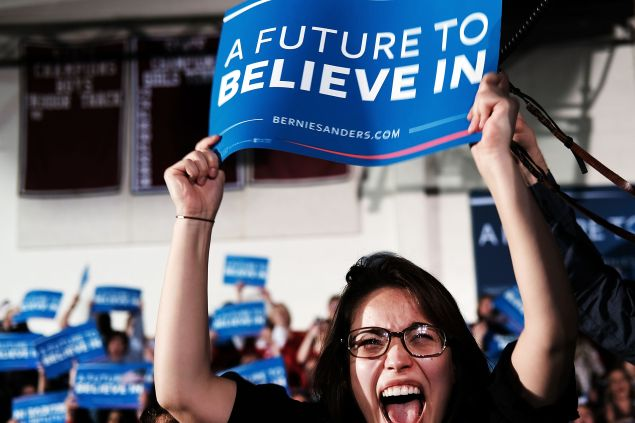 CONCORD, NH - FEBRUARY 09: People cheer as Democratic presidential candidate Sen. Bernie Sanders (D-VT) speaks onstage after victory over Hillary Clinton in the New Hampshire primary on February 9, 2016 in Concord, New Hampshire. Sanders was projected Democratic winner shortly after the polls closed. (Photo by Spencer Platt/Getty Images)