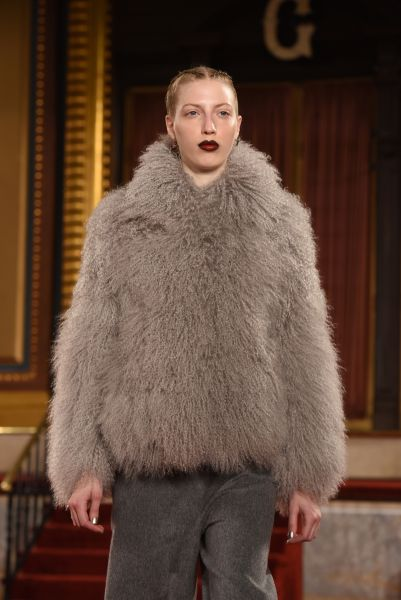 A grey Mongolian coat plays well with a bold lip (Photo: Noam Galai/Getty Images).