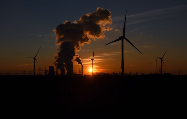 Electricity pylons and wind turbines stand beside the RWE Niederaussem coal-fired power plant while Steam rises from cooling towers on February 16, 2016 near Bergheim, Germany.