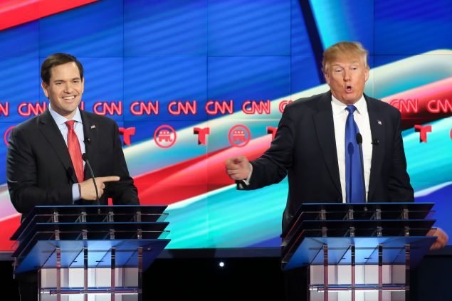 Marco Rubio, left, listens as Donald Trump answers a question during the Republican Presidential Primary Debate at the University of Houston Thursday, Feb. 25, 2016.