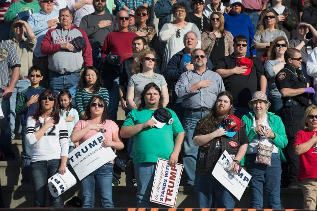 Guests listen to the national anthem during a campaign rally for Republican presidential candidate Donald Trump at the Madison City Schools Stadium on February 28, 2016 in Madison, Alabama. Trump is in Alabama ahead of the Super Tuesday primaries March 1.