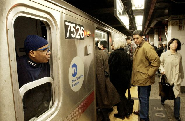 NEW YORK, UNITED STATES: A conductor on the number 6 line of the New York City subway (L) watches passengers board the train 13 December, 2002, at Grand Central Terminal in New York. The 34,000 member Transit Workers Union is threatening a strike if their contract with the Metropolitan Transit Authority expires at 12:00 AM, 16 December, shutting down subway and bus service across the city. AFP PHOTO/Stan HONDA (Photo credit should read STAN HONDA/AFP/Getty Images)