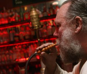 John Garbarini takes a drag on a hookah pipe at Karma, one of the few bars where smoking is still allowed in the East Village, in 2008.