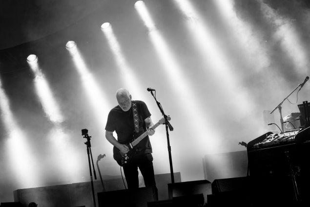 """David Gilmour's 70,000 fans gather for his first ever concert in Buenos Aires Hipódormo de San Isidrio, Argentina. The singer-songwriter decided to craft a setlist blending his own solo material with highly anticipated and well-loved Pink Floyd tunes. The first half of the gig brought the audience Dark Side of the Moon classics """"Us & Them"""" and """"Money"""" along with solo cuts """" 5 A.M.,"""" """"In Any Tongue"""" and """"A Boat Lies Waiting"""" from his latest studio album, Rattle That Lock. The show saw a similar second set of debut album track """"Astronomy Domine,"""" Atom Heart Mother's """"Fat Old Sun"""" and Wish You Were Here fan favorite, """"Shine On You Crazy Diamond."""" As the set continued, the 69-year-old guitar legend rolled out more solo material off of his fourth studio album including """"The Girl in the Yellow Dress,"""" """"Today,"""" and """"On An Island"""" trailed by his former group's """"Sorrow"""" and The Wall track, """"Run Like Hell."""" Ref: http://www.musictimes.com/articles/58329/20151215/david-gilmour-launches-tour-south-america-mixing-solo-material-classic-pink-floyd.htm El guitarrista y cantante de Pink Floyd, David Gilmour, tocó el viernes por primera vez en la Argentina y brindó un memorable concierto de casi tres horas, ante unas 60 mil personas, en el Hipódromo de San Isidro, en el que revivió la magia del popular conjunto inglés. ...el excelso guitarrista mostró prácticamente todas las canciones de su último trabajo (titulado Rattle that lock) y recreó algunas de las más brillantes composiciones popularizadas por el cuarteto que integró junto a Roger Waters, Richard Wright y Nick Mason. La primera gran ovación de la noche estalló cuando empuñó una guitarra acústica y desgranó las primeras notas de Wish you were here, el clásico grabado en el disco homónimo de 1975. El espíritu de Dark side of the moon, la obra maestra editada en 1973, prosiguió con Us and them, la emocionante canción que hace referencia a la alienación, y luego de interpretar In any tongue y High H"""