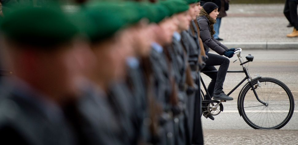 "A bicycle commuter travels past a guard of honour during a wreath laying ceremony by Italian President at the ""Neue Wache"" memorial for victims of conflict and war in Berlin on March 1, 2013. AFP PHOTO / ODD ANDERSEN"