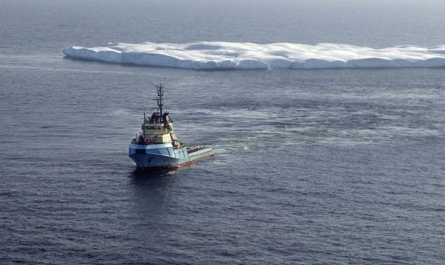 A tug tows an iceberg to safer waters and away from a possible collision with an oil-drilling platform off the coast of Newfoundland in the north Atlantic Ocean.