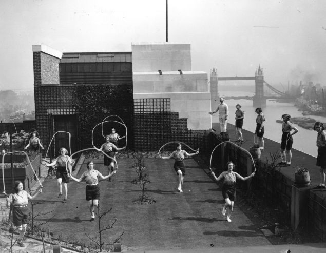 A slimming class of office girls performing skipping exercises on the roof of Adelaide House, London, during their lunch hour.