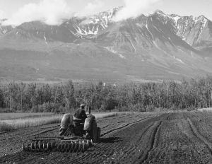 A tractor ploughs the land at the foot of a mountain in western Canada, 1950.