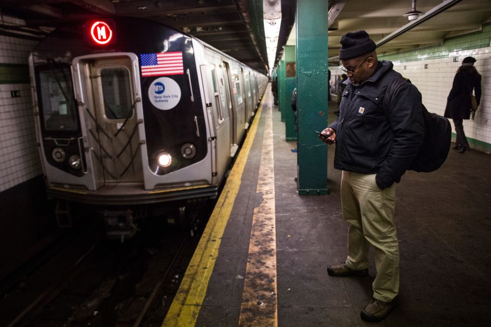 A man waits for a downtown M train. (Photo by Andrew Burton/Getty Images)