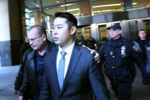 New York City police officer Peter Liang is escorted out of court after he was charged with manslaughter, official misconduct and other offenses on February 11, 2015.