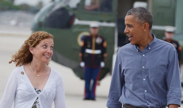 US President Barack Obama chats with DNC chair Debbie Wasserman Schultz as he makes his way to Air Force One shortly before departing from Miami International Airport in Miami on April 22, 2015.