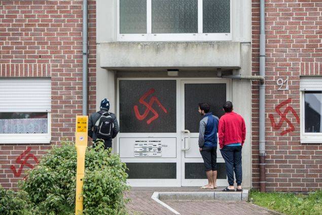 Men look at a swastika sprayed at a asylum seeker accommodation in Waltrop, western Germany, on October 13, 2015. Four homes for asylum seekers in Waltrop were sprayed with swastikas during the night from October 12 to 13, 2015. AFP PHOTO / DPA / MAJA HITIJ GERMANY OUT