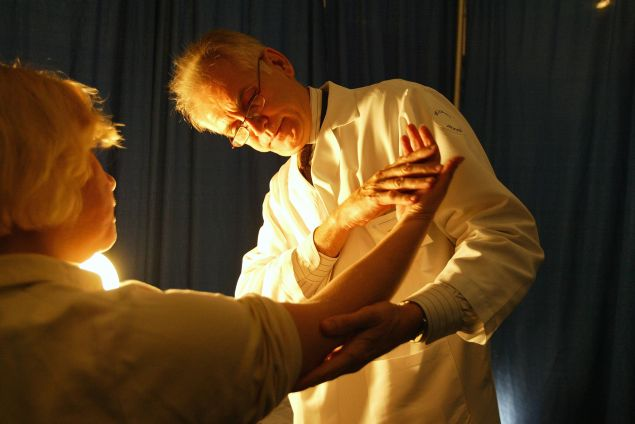 A doctor from the American Academy of Dermatology performs a free cancer screening on a patient.