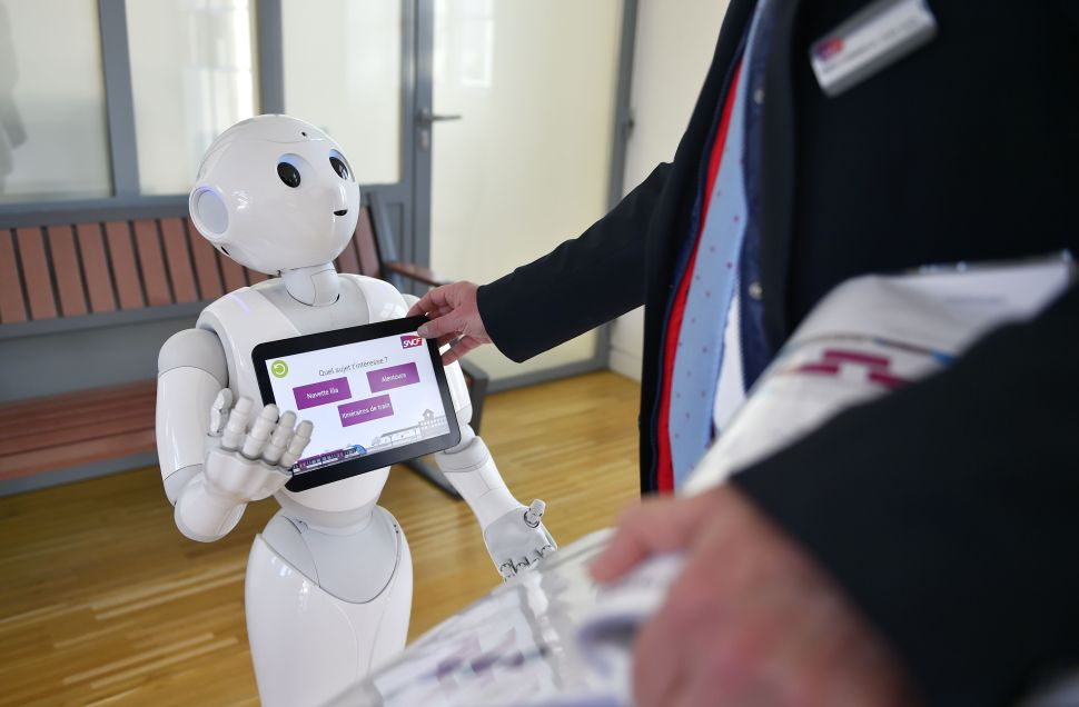 "TO GO WITH AFP STORY BY JEAN LIOU A SNCF agent makes settings on ""Pepper"", a humanoid robot which delivers information to users of the French railway company SNCF, on March 2, 2016 at the Nort-sur-Erdre train station, western France. Made by French firm Aldebaran, Japanese group SoftBank's subsidiary, Pepper has been installed in December in three stations in the Pays de la Loire region. / AFP / LOIC VENANCE"