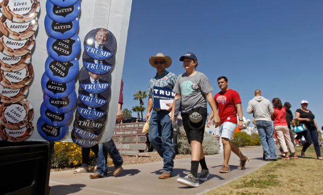 Supporters of Republican presidential candidate Donald Trump walk past campaign buttons during a campaign rally at Fountain Park on March 19, 2016 in Fountain Hills, Arizona. Trump visits Arizona for the second time in three months as he looks to gain the GOP nomination for President.