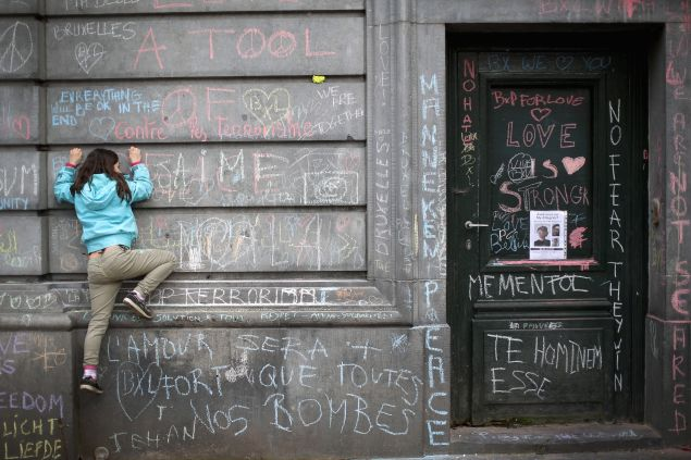 A young girl climbs a wall to chalk a message of support on the the Bourse De Brussels building in the Place de la Bourse following yesterday's terrorists attacks on March 23, 2016 in Brussels, Belgium. Belgium is observing three days of national mourning after 34 people were killed in a twin suicide blast at Zaventem Airport and a further bomb attack at Maelbeek Metro Station. Two brothers are thought to have carried out the airport attack and an international manhunt is underway for a third suspect. The attacks come just days after a key suspect in the Paris attacks, Salah Abdeslam, was captured in Brussels.