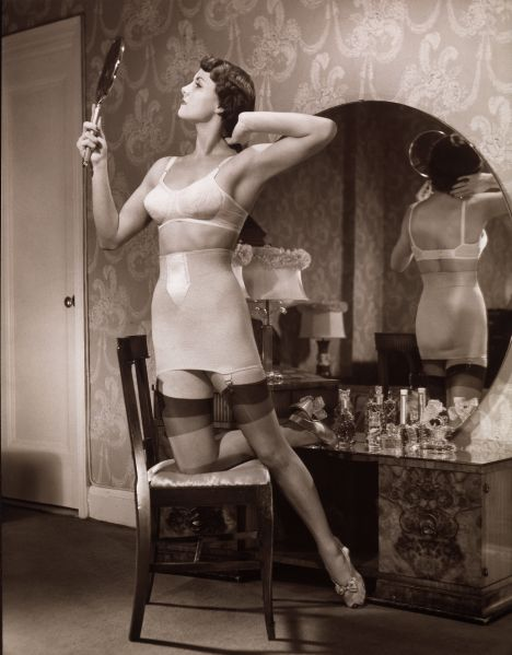 A woman kneels in a chair dressed in her brassiere and stockings, admiring herself in a hand mirror and arranging her hair, 1940s.