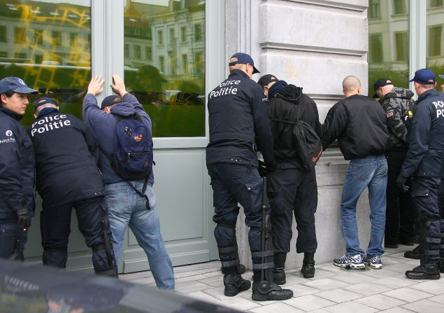 Belgian police officers arrest anti-Islam demonstrators.