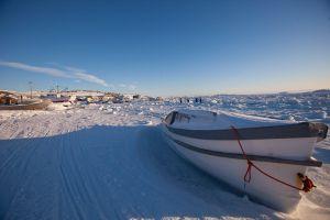 A boat sits along the frozen shoreline in Iqaluit, Canada.