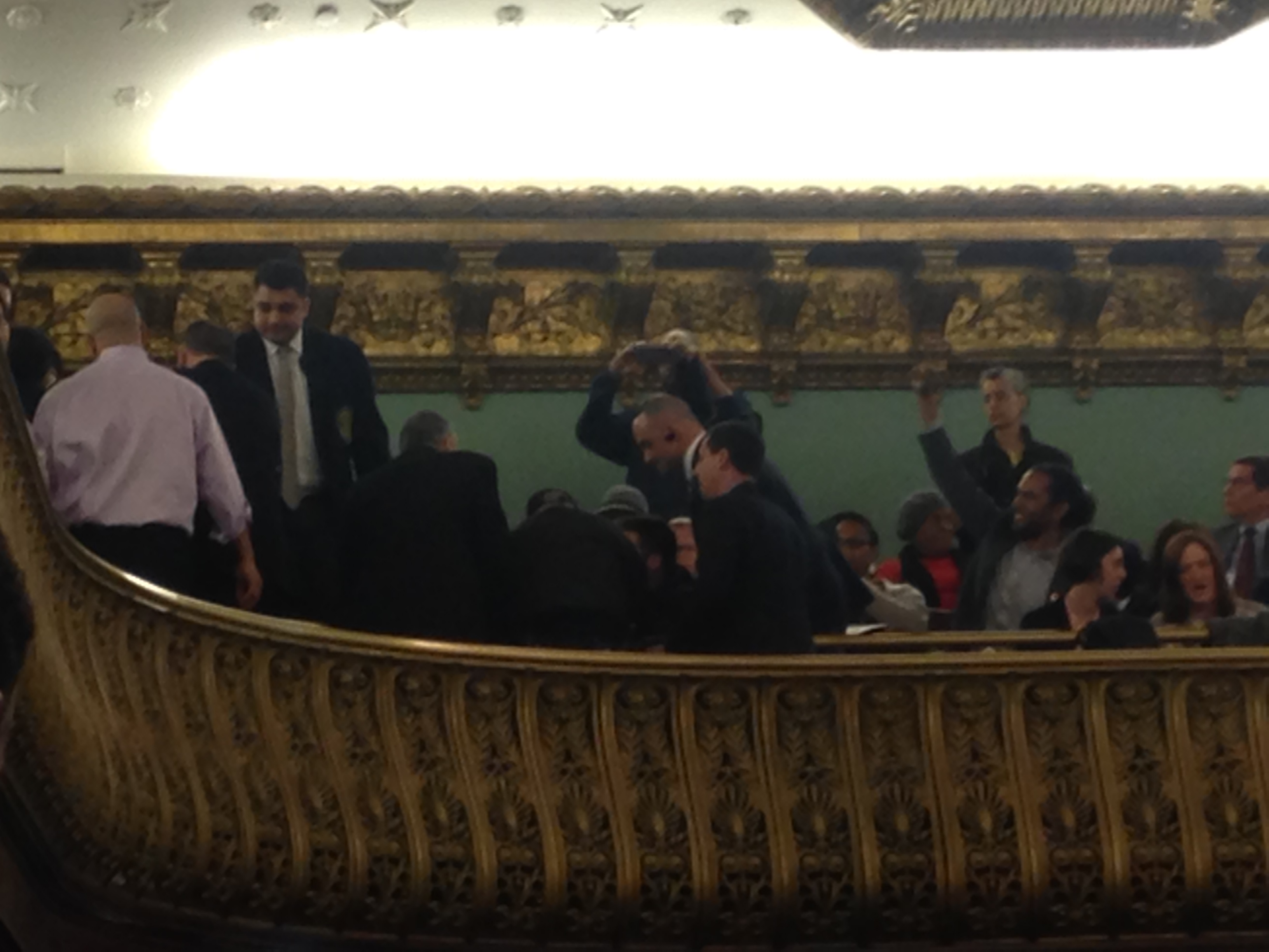 Council security and police try to pry protesters from their seats in the balcony.