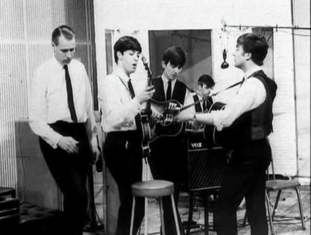 George Martin and the Beatles in the studio.