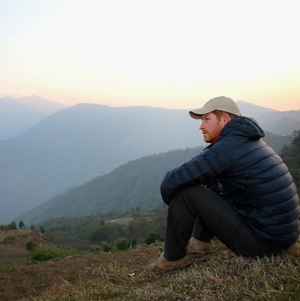 Prince Harry hiking near a remote village
