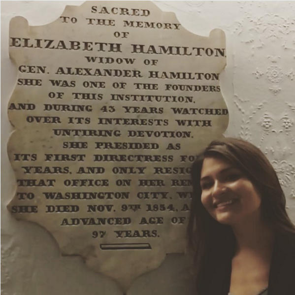 Phillipa Soo posing with a plaque dedicated to Elizabeth Hamilton, her character in the broadway musical Hamilton.