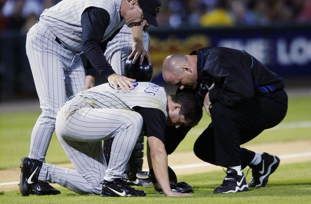 ST. LOUIS - SEPTEMBER 23: Manager Bob Brenly of the Arizona Diamondbacks and team trainer Paul Lessard check on third baseman Chris Donnels #18 after Donnels suffered a mild concussion while fielding a bunt in the third inning of the MLB game against the St. Louis Cardinals on September 23, 2002 at Busch Stadium in St. Louis, Missouri. The St. Louis Cardinals beat the Arizona Diamondbacks 13-1. (Photo by Elsa/Getty Images)