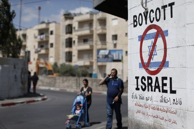 Palestinians walk past a sign painted on a wall in the West Bank biblical town of Bethlehem on June 5, 2015, calling to boycott Israeli products coming from Jewish settlements. The international BDS (boycott, divestment and sanctions) campaign, that pushes for a ban on Israeli products, aims to exert political and economic pressure over Israel's occupation of the Palestinian territories in a bid to repeat the success of the campaign which ended apartheid in South Africa. AFP PHOTO / THOMAS COEX