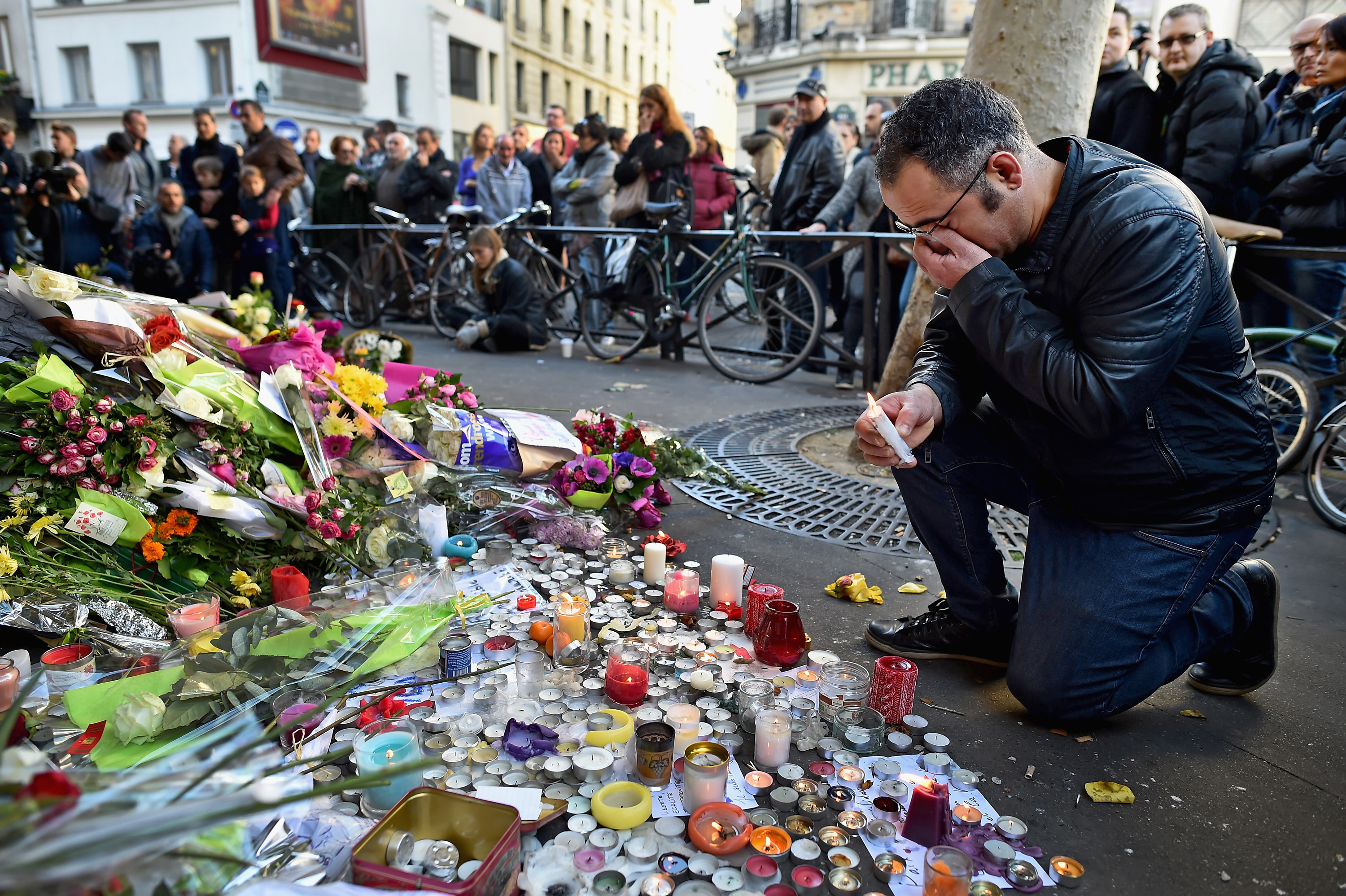 A man mourns the dead in the November 2015 Paris terrorist attacks gather at a memorial outside the La Belle Equipe restaraunt on Rue de Charonne, one of the locations where gunmen massacred innocents.