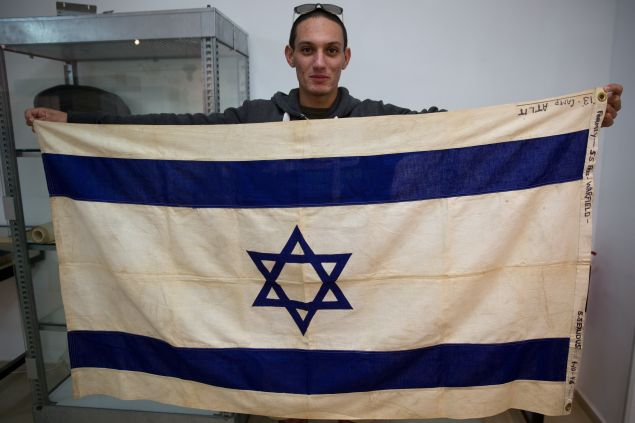 An employee of the Kedem Auction House in Jerusalem on November 15, 2015 shows the flag of the iconic ship the SS Exodus, the most famous of hundreds of ships that sought to transport European Jews to the land that later became the nation of Israel immediately after World War II. The flag will be sold at a public auction in December for at least 100,000 US dollars. AFP PHOTO/MENAHEM KAHANA