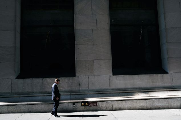 A man walks by the New York Stock Exchange (NYSE) along Wall Street on March 21, 2016 in New York City. Following a strong week for US stocks, the Dow Jones industrial average was down slightly in morning trading.