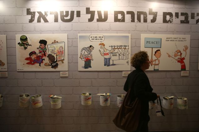 A woman walks past caricatures of Israeli artists against the Palestinian-led Boycott, Divestment and Sanctions (BDS) movement displayed during the Ynet and Yedioth Ahronoth's anti-BDS conference on March 28, 2016, in Jerusalem.
