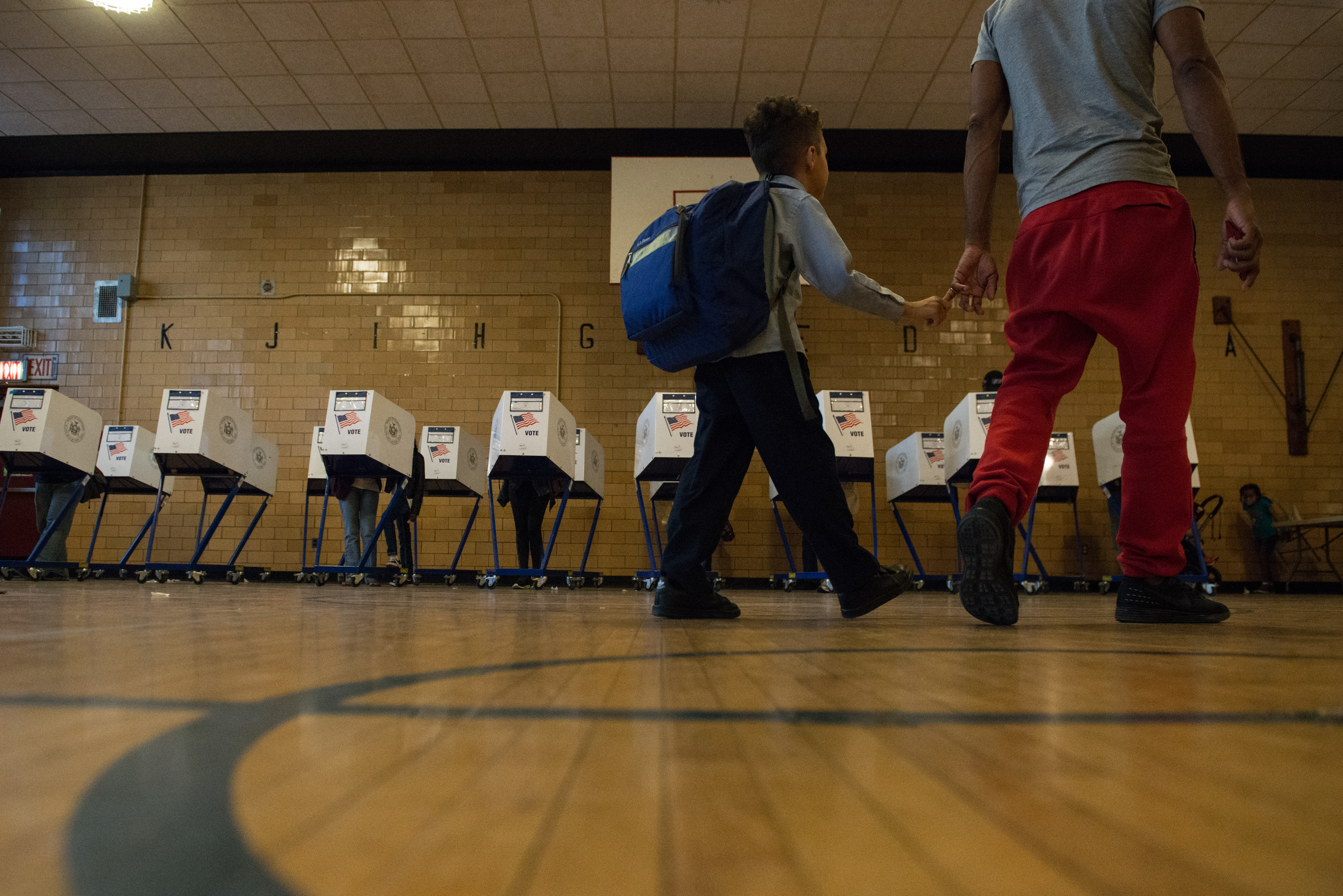A man with his son walk past voting booths at Public School 22 in Brooklyn on Tuesday.