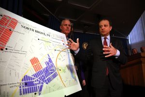 United States attorney Preet Bharara gestures at a map showing where 120 people were arrested on gang-related charges in the Bronx