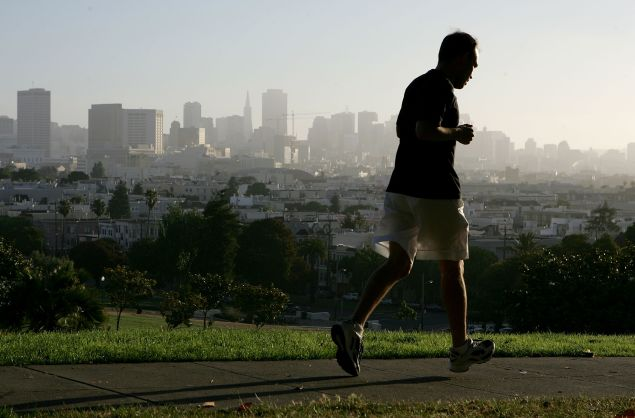 With the San Francisco skline in the background, a jogger runs through Dolores Park July 13, 2005 in San Francisco. Runner's World Magazine has just named San Francisco the best city for running in the United States based on its weather, the number of running clubs, racing events and the the ample park space available for runners.
