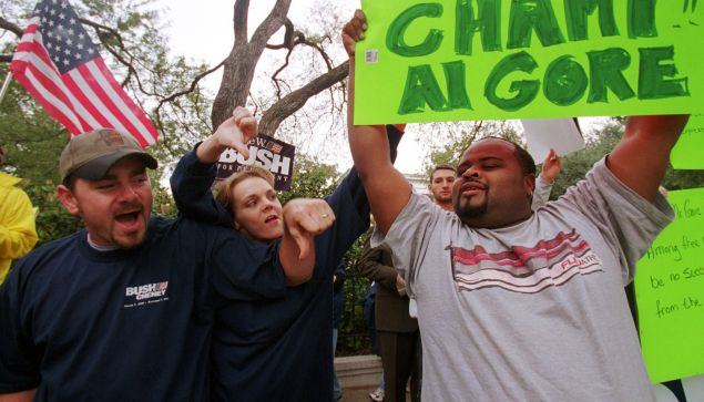"""381733 07: Victor Reed, right, a pro-Gore supporter, is yelled at by pro-Bush supporters outside the Texas governor's mansion November 11, 2000, in Austin, Texas. Bush, spending the weekend at his ranch, complained about the state of the presidential election being in """"limbo."""" (Photo by Joe Raedle/Newsmakers)"""