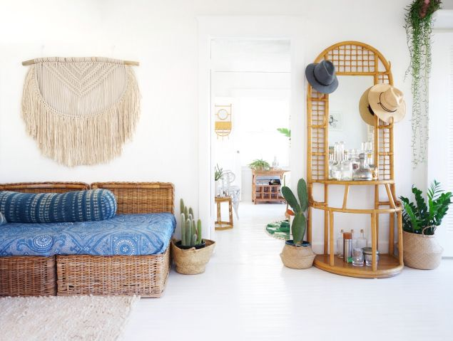 A hand-knit macrame from Australia hangs on the wall; a vintage rattan bar invites guests to don a hat.