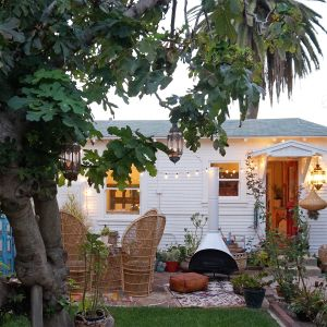 String lights and lanterns adorn the front yard of the cozy cottage.