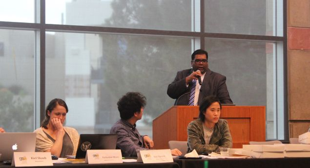 UCLA graduate student president Milan Chatterjee, standing, defends himself against accusations brought by Katherine Myers, first from left.