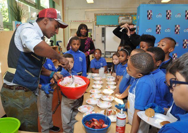 Marcus Samuelsson shows children at East Harlem Scholars Academy how to make yogurt parfaits