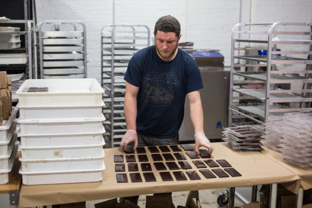 A worker at Rakka Chocolate factory in Red Hook, Brooklyn, lays out freshly made chocolate bars. 5/24/2016 - Photo by Aaron Adler for The Commercial Observer
