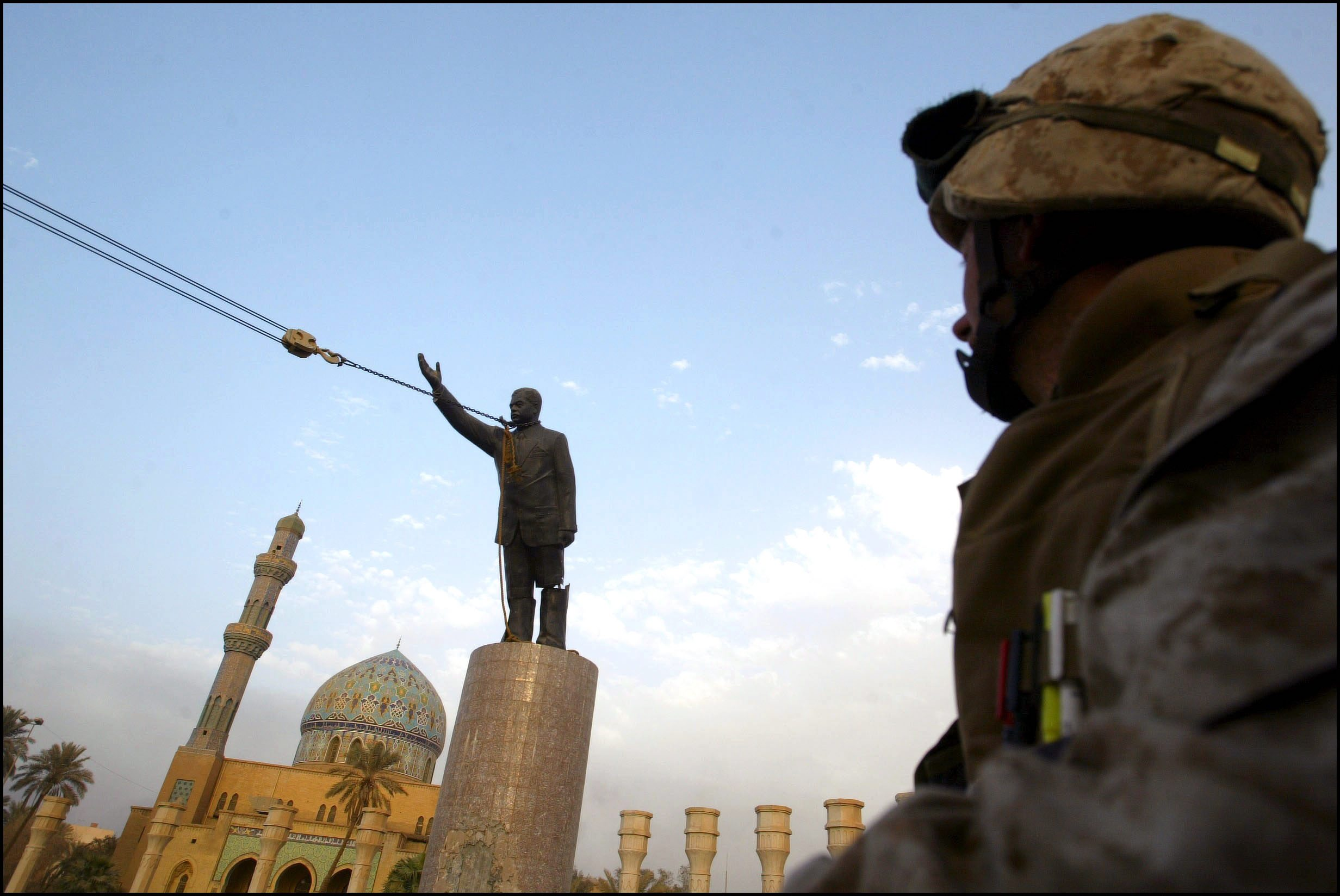 U.S. Marine watches as statue of Saddam Hussein topples in 2003.